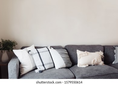 White living room wtih grey couch and set of white and grey striped pillows, house plant in the corner