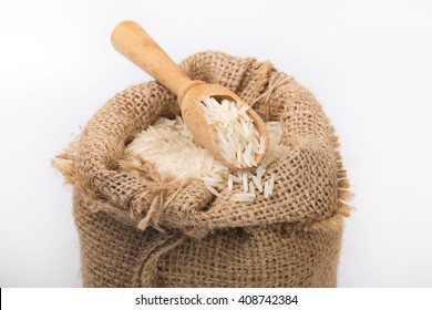 White long rice in burlap sack with wooden spoon inside. Small DoF. Soft focus. Closeup composition.