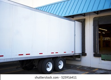 White long semi trailer with an open door stand close in the warehouse dock with a green sloping roof to unload a cargo delivered to this location.