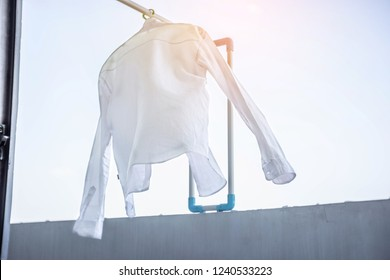 white  Long sleeve shirt collar hanging on a clothesline in front of sky and sun