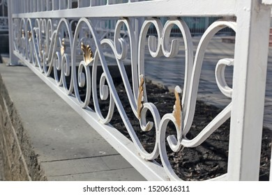 White low wrought iron fence with scrollwork patterns