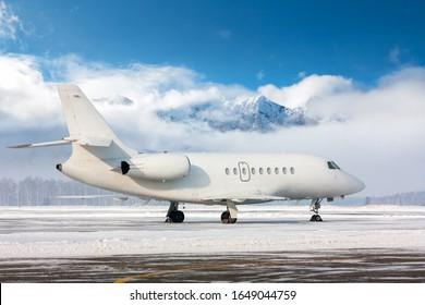 Weißer Luxus-Business-Jet auf dem Winterflughafen auf dem Hintergrund der Hochlandberge an einem klaren sonnigen Tag