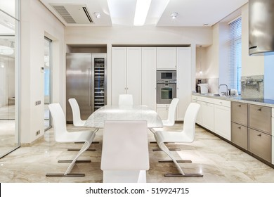 White luxury kitchen in a modern house with stone floors and white furniture