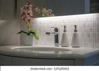 white luxury marble bathroom sink/ washbasin with satainless faucet , soap dispenser and orchit flower pot on top of the countertop.