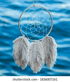 White Macrame Dreamcatcher with Blue Water in the Background