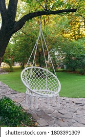 White macrame swing hanging in the garden. Summer outdoor garden background.