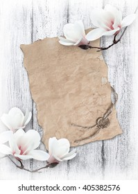 White magnolia and old paper with sealing wax on background of shabby wooden planks