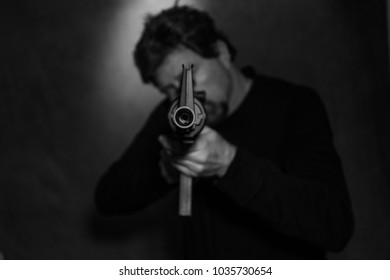white male aiming an assault rifle directly at camera - black and white