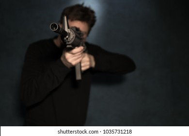 white male aimming an assault rifle to the left of camera. Color photo.