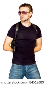 White male dressed in black on an isolated background wearing a shoulder holster armed with an revolver