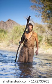 White Male Dressed as Jesus in Jewish Attire. Others as John the Baptist/ Prophet with burlap clothes and wood staff near river.