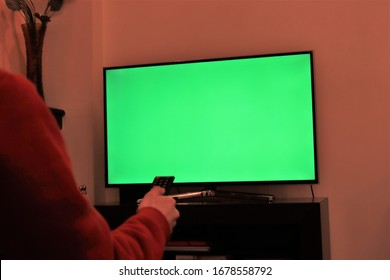 A white male hand using remote controller over a green screen television late in the night.green screen on smart tv.Place for your advertisment.modern television set-Athens Greece March 23 2020