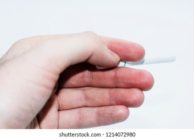 A white male holding a cigarette with a white filter. Isolated on a white studio background.