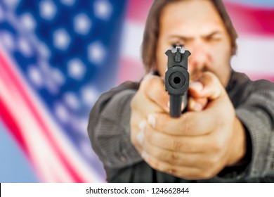 White male holding a handgun with the american flag as a backdrop.