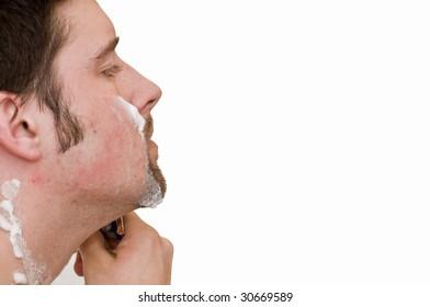 White male shaving his face