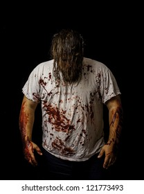white male wearing a white shirt covered in blood with his hair covering his face.
