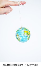 A white male's finger with a globe on a string. Symbolic