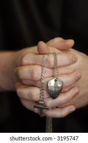 White male's hands clasped with necklaces with crosses with the name Jesus engraved in one