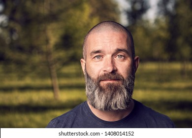 A white man about 43 years old with short hair and beard has a rest in a park, close-up.