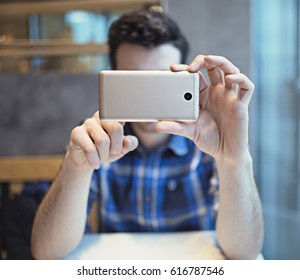 White man with dark hair makes a photo on the camera on his smartphone