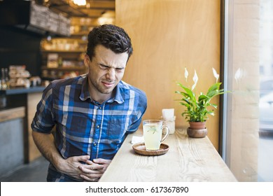 A white man with dark hair sits at a wooden table near the window in a blue shirt and has a very bad stomach ache