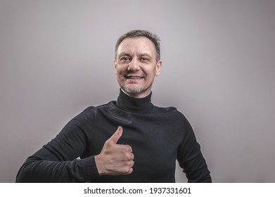 A white man of European appearance middle aged with gray in his hair and a slightly unshaven face in a black turtleneck happily gives a thumbs up