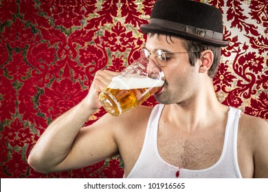 White man with glasses, hat, wife beater, brown hair chugging light beer alone in retro red and gold background bar