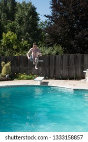 White man jumping into an outdoor swimming pool in the summer. Man doing cannon ball into backyard swimming pool on a sunny day.  Jumping off diving board doing cannon ball into a pool.