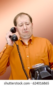 A white man in an orange shirt and glasses with a telephone receiver in the rivers looks at the old disk-type wired telephone with surprise and bewilderment