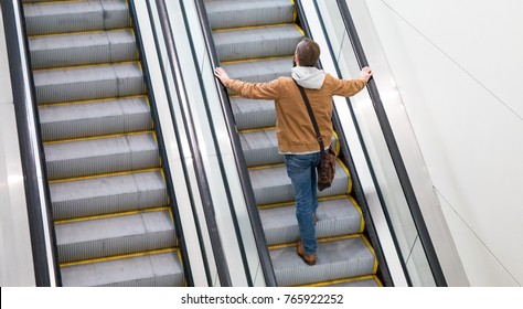 A white man riding up an indoor escalator.
