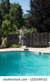 White man running to the edge of a diving board to jump into an outdoor swimming pool in the summer. Fit man on diving board in backyard swimming pool wearing blue swimming trunks ready to jump.