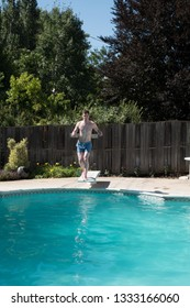 White man running to the edge of a diving board to jump into an outdoor swimming pool in the summer. Fit Caucasian man on diving board in backyard swimming pool wearing blue swimming trunks.