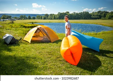 White man setting up inflatable sofas out in the wild camping
