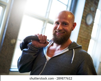 White man smiling at camera lifting a kettlebell for strength training