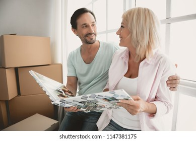 White Man and Woman Seated at Window of New Apartment Next to Cardboard Boxes and Reviewing their Family Album. Memories in Photo. Empty Apartment. Young Man in Room. New Apartment Concepts.