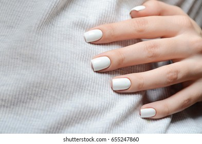 White manicure on the background of the gray t-shirt
