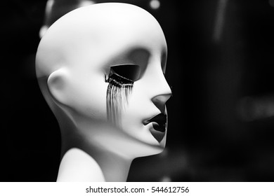 White mannequin head with bottom black eyelashes and black lips.