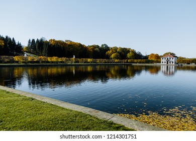 White mansion in the garden near the water and fountains. White two-storey house by the pond in the autumn garden.