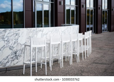 White marble bar counter with high chairs on the background of modern building in minimalist style