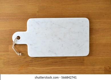 White marble cheese board in a kitchen with cheese and grapes