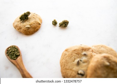 White Marble of Edible Marijuana Chocolate Chip Cookies, Cannabis Buds and Ground Weed on a Wooden Spoon