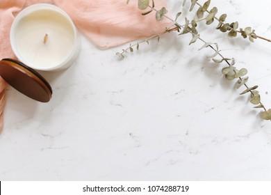 White marble flat lay with blush textiles and eucalyptus.