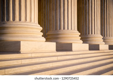White marble neoclassical columns of the portico of the Supreme Court of the United States building in soft sunset light in Washington DC, USA