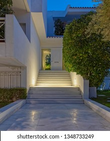 white marble pathway and illuminated stairs to modern house entrance through the garden, night view