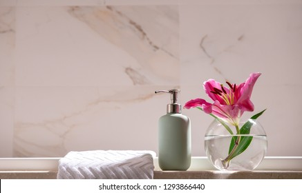 White Marble Shelf Table Top can used for display or montage your products. Pink Lily Flower in Glass Vase White Towel Soap Dispenser Luxury Bathroom interior Cleanliness Beauty Concept Copy Space