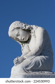 white marble statue on tombstone of sad girl against a deep blue sky, from side angle