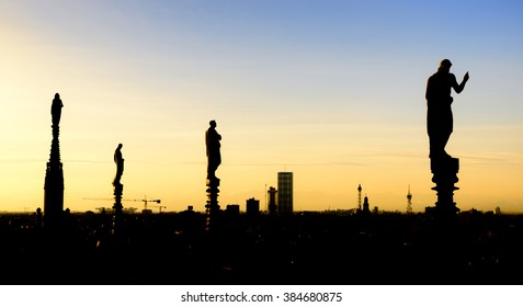 White marble statues on the roof of famous Cathedral Duomo di Milano on piazza in Milan, Italy