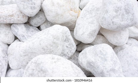 White marble stones. White abstract background with texture of white marble stones. Exterior and interior decoration with natural tumbled marble stones.
