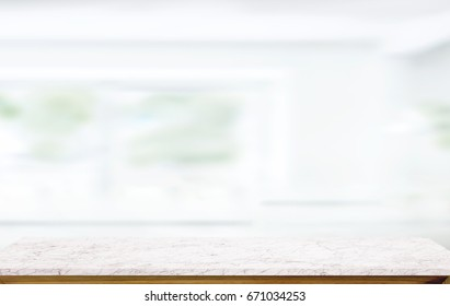 White marble table top on blur kitchen window background. For product or foods montage.