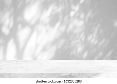 White Marble Table with Tree Shadow on Concrete Wall Texture Background, Suitable for Product Presentation Backdrop, Display, and Mock up.